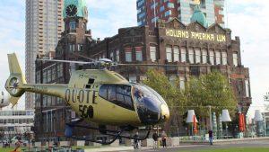 Helikopter Eurocopter Ec120 HeliCentre PH-UNN vliegt voor de Quote 500 bij Hotel New York te Rotterdam