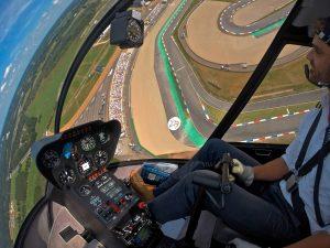 Helikopter Robinson R44 Raven II PH-JPS HeliCentre vliegend boven TT Circuit Assen